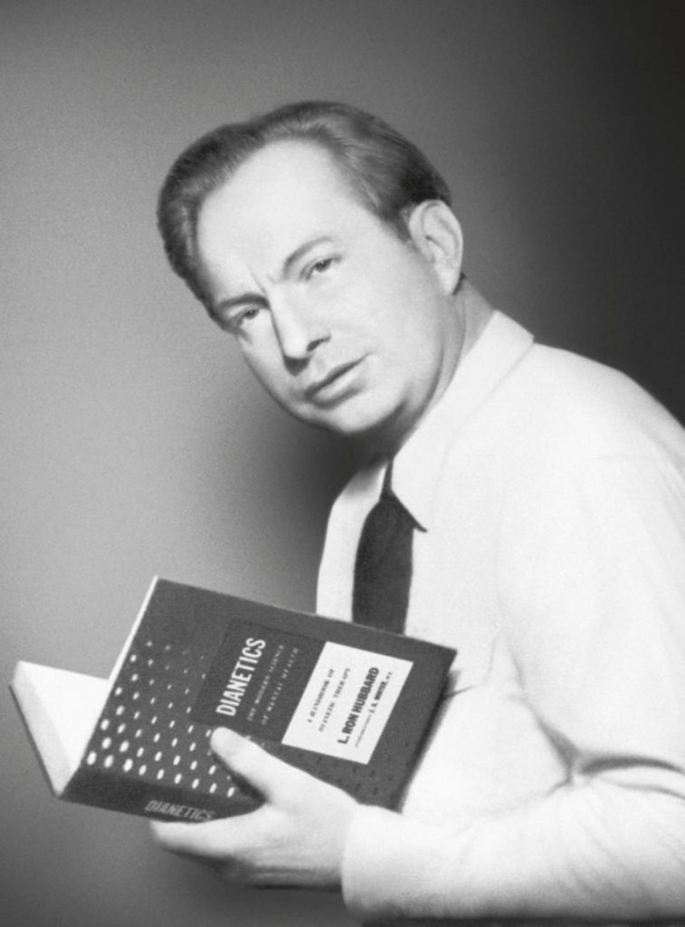 Л. Рон Хаббард с первым изданием книги Дианетика